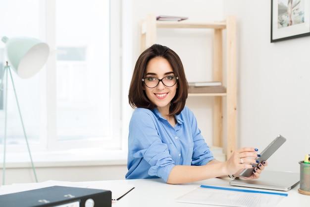 블루 셔츠에 예쁜 갈색 머리 소녀는 사무실 테이블에 앉아있다. 그녀는 노트북으로 작업하고 카메라에 웃고.