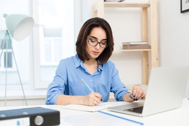 예쁜 갈색 머리 소녀는 사무실 테이블에서 일하고있다. 그녀는 파란색 셔츠와 검은 색 안경을 쓰고 있습니다. 그녀는 진지하게 글을 쓰고 있습니다.