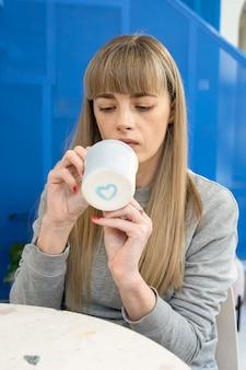 예쁜 백인 여성이 연인을 위해 머그를 칠하고 컵 바닥에 파란 하트가 그려져 있다