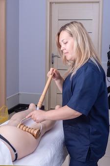 Симпатичная кавказская массажистка массирует заднюю часть бедра пациента деревянным роликовым массажером на вертикальной раме.