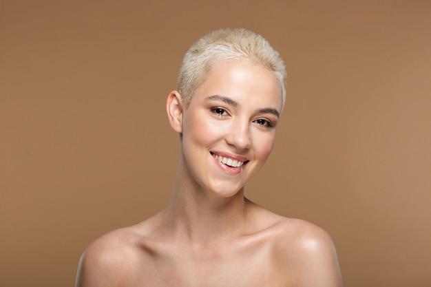 Довольно жизнерадостная улыбающаяся молодая блондинка стильная женщина с короткой стрижкой позирует изолированной над темно-бежевой стеной.