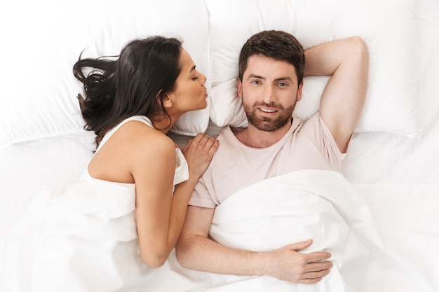 かわいらしい若い愛情のあるカップルが毛布の下のベッドに横たわっています
