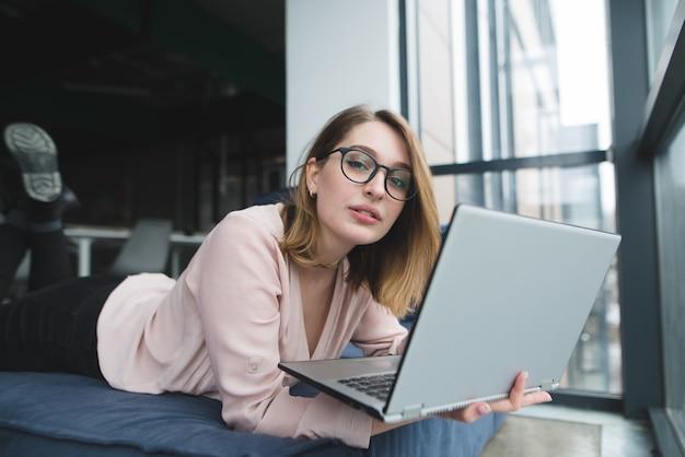 안경에 예쁜 여자는 그녀의 손에 노트북과 함께 소파에 창에 놓여 카메라를 찾습니다