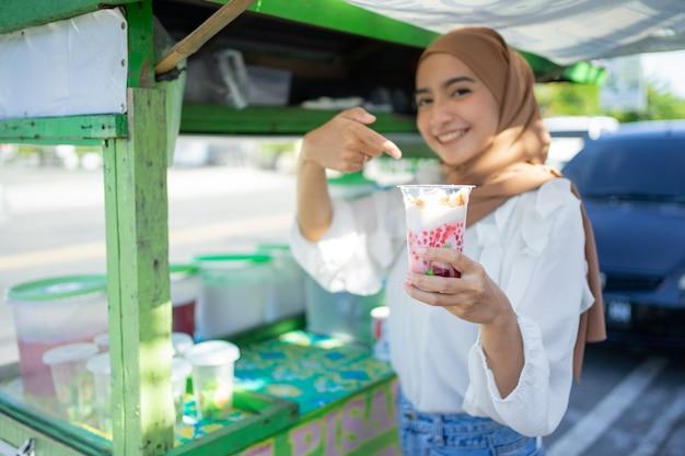 Симпатичная девушка в чадре продавца es campur показывает пальцем на пластиковую чашку восхитительного е ...