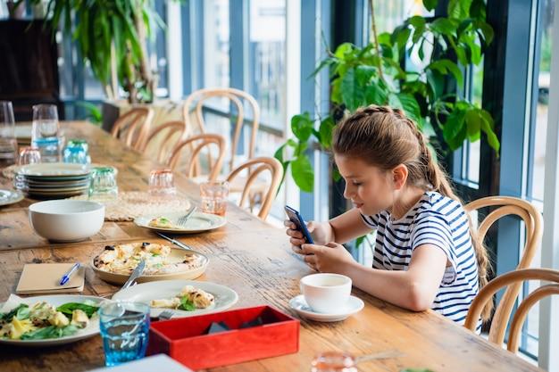 キッチンで彼女のスマートフォンで遊ぶかわいい女の子