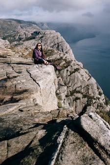 Красивая девушка сидит на вершине горы прекестулен (кафедра) в норвегии.