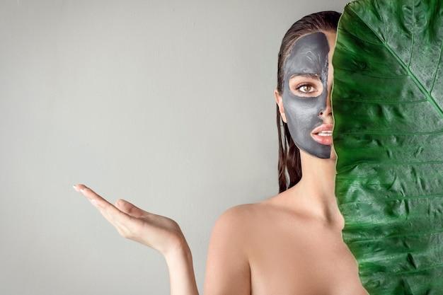 粘土の保湿マスクを適用し、緑の葉を保持しているかわいい女の子。スパ。