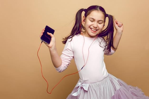 Симпатичная маленькая девочка слушает, размышляет в наушниках, с закрытыми глазами, движется