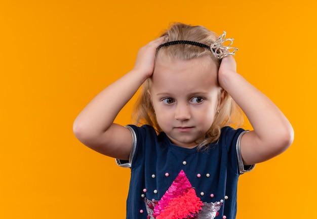 Симпатичная маленькая девочка в темно-синей рубашке в головной повязке с короной держится за голову и смотрит сбоку на оранжевую стену