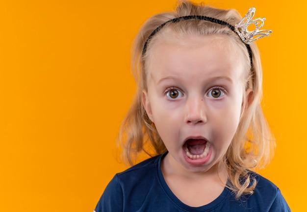 Симпатичная маленькая девочка в темно-синей рубашке в головной повязке с короной открывает рот и смотрит на оранжевую стену