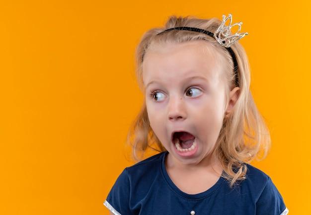 Симпатичная маленькая девочка в темно-синей рубашке в головной повязке с короной, открывая рот и глядя сбоку на оранжевую стену