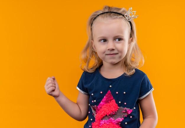 Симпатичная маленькая девочка в темно-синей рубашке в головной повязке с короной поднимает сжатый кулак и смотрит сбоку на оранжевую стену