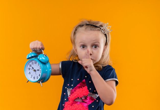 オレンジ色の壁に青い目覚まし時計を保持しながらshhジェスチャーを示す王冠のヘッドバンドで紺色のシャツを着ているかわいい女の子