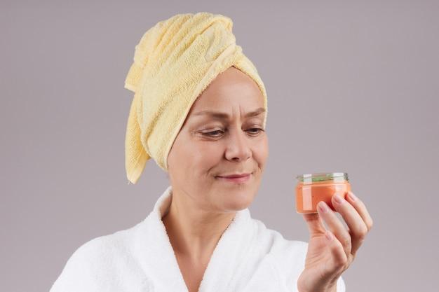 オレンジ色のクリームの瓶を持って、彼女の頭に黄色いタオルを着たガウンを着たかなり成熟した女性。フェイシャルスキンケアのコンセプト。灰色の壁を越えて。