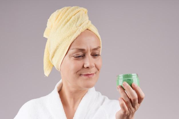 緑のフルーツクリームの瓶を持って、ローブを着たかなり成熟した女性、頭に黄色いタオル。フェイシャルスキンケアのコンセプト。灰色の壁を越えて。