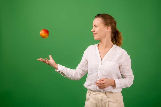 흰 셔츠를 입은 예쁜 중년 여성이 녹색 배경에 신선한 사과를 던졌습니다. 건강 식품, 채식주의의 개념입니다.