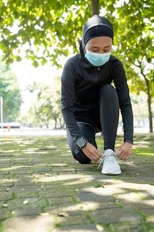 Симпатичная мусульманка-спортсменка растягивается и тренирует свое тело на открытом воздухе и носит маску для защиты от вируса