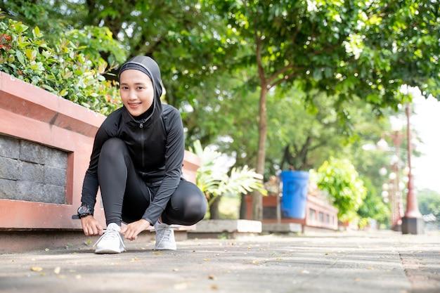 Симпатичная мусульманка-спортсменка связывает туфли перед бегом на свежем воздухе