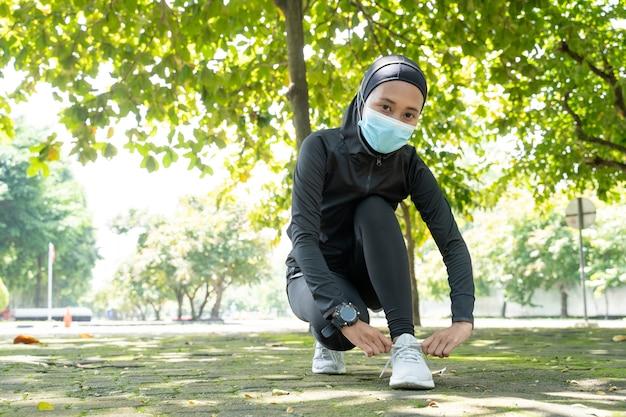 Симпатичная мусульманка-спортсменка с маской для лица завязывает обувь перед бегом на свежем воздухе
