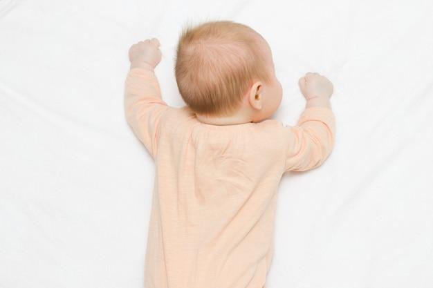 Симпатичная новорожденная малышка в бежевом боди лежит на животе на легком одеяле