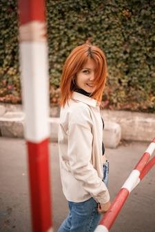 かなり赤毛の若い女性が通りを歩いていて、彼女はジーンズとベージュのシャツを着ています。笑顔でカジュアルな装いの美少女