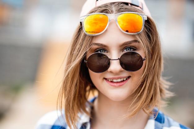 Довольно улыбающаяся белокурая девушка в клетчатой рубашке и двух солнцезащитных очках смотрит игривыми глазами.