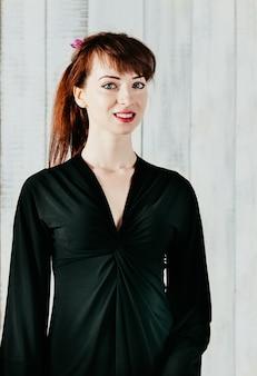 Довольно улыбается женщина в черном платье, на светлом фоне