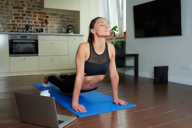 Симпатичная спортивная девушка в черном обтягивающем костюме делает упражнения на растяжку и смотрит онлайн-обучающее видео на ноутбуке. тренер проводит дистанционное занятие фитнесом на синем коврике для йоги дома.