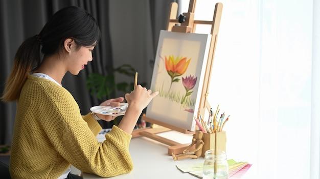 Довольно талантливая художница с палитрой в руках рисует на холсте в студии