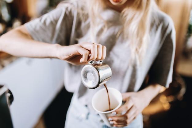Довольно худая блондинка с длинными волосами, одетая в повседневную одежду, наливает кофе в стакан в уютной кофейне. .