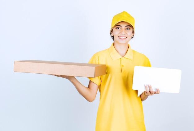 茶色の空白のクラフト紙箱と空白の吹き出しを持っているきれいな女性。