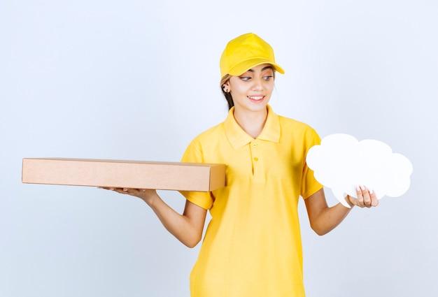 Симпатичная женщина, держащая коричневую пустую бумажную коробку ремесла и пустой речевой пузырь.