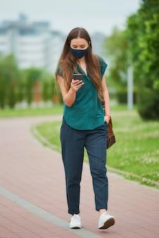 파란 해군 얼굴 마스크에 예쁜 여자가 바지 주머니에 손을 밀어 넣는 스마트 폰 뉴스를 읽습니다. 공원에서 산책합니다.