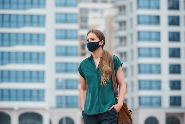 의료 얼굴 마스크에 예쁜 여자가 걷는 동안 바지 주머니에 손을 밀고있다