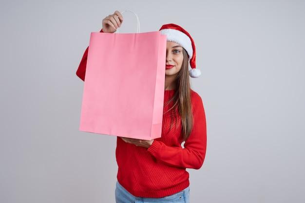 쇼핑 가방 뒤에 숨어있는 빨간 스웨터에 산타 모자에 예쁜 여자. 크리스마스 판매, 쇼핑, 할인의 개념.