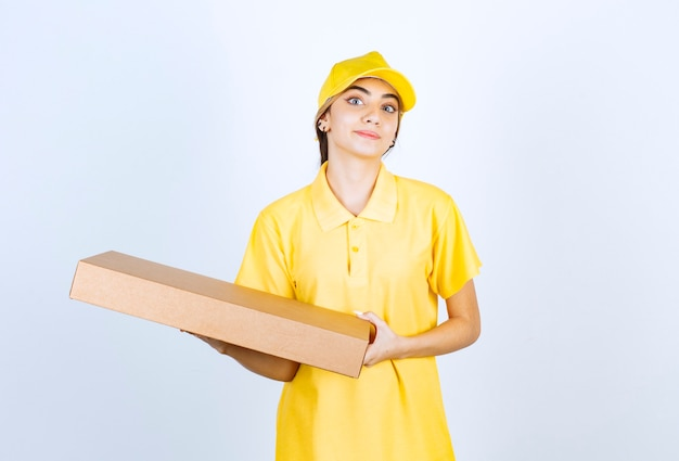 Красивая женщина в желтой форме держит коричневую пустую бумажную коробку.