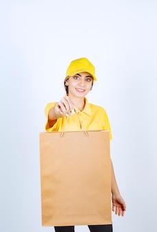 Красивая женщина в желтой форме держит коричневый пустой бумажный пакет.