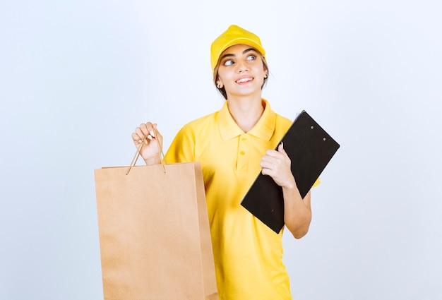 갈색 빈 공예 종이 가방을 들고 노란색 유니폼에 예쁜 여자.