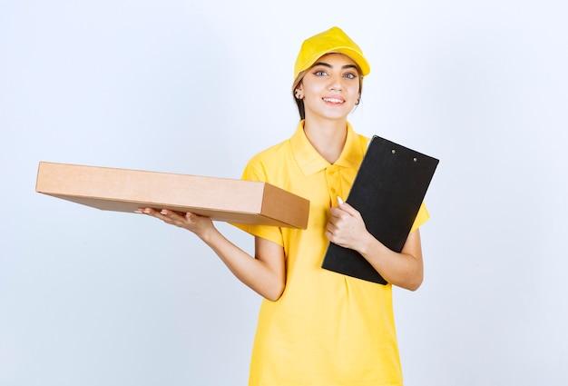 フォルダー付きの茶色の空白のクラフト紙箱を保持している黄色の制服を着たきれいな女性。