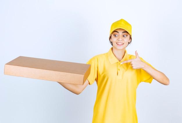 茶色の空白のクラフト紙箱を指している黄色の制服を着たきれいな女性。