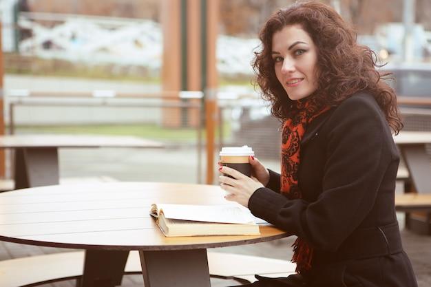Красивая женщина увлеченно читает книгу на террасе уличного кафе с кружкой горячего кофе