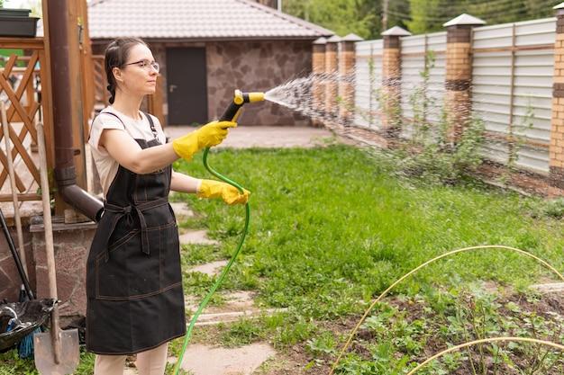 예쁜 여자가 정원에서 꽃과 묘목에 물을 주고 있다