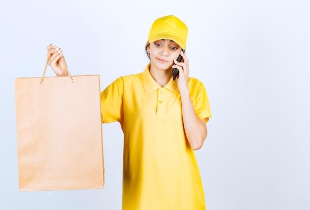 Красивая женщина разговаривает по телефону и держит коричневый пустой бумажный пакет.