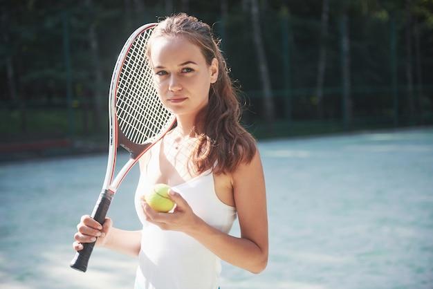 コートでスポーツウェアのテニスコートを着ているきれいな女性。