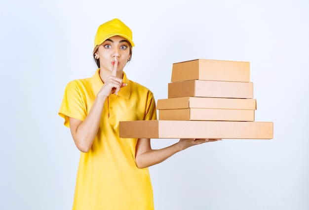 サイレントサインを示す茶色の空白のクラフト紙箱を持つきれいな女性。