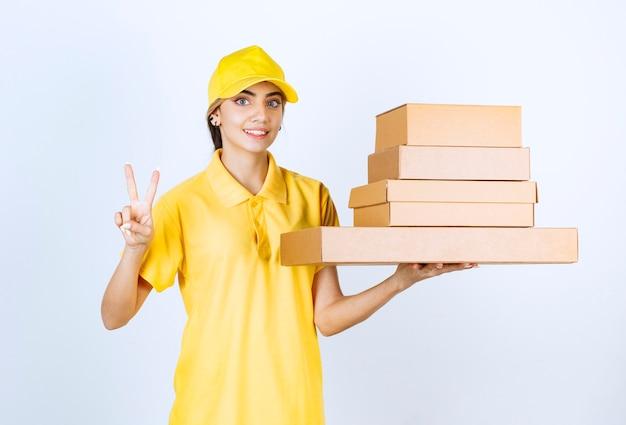 勝利のサインを示す茶色の空白のクラフト紙箱を持つきれいな女性。