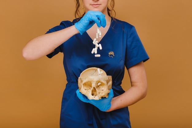 かなり若い医者が人間の頭蓋骨にビタミンカプセルを注ぎます。医者は背景に丸薬を注ぎます。