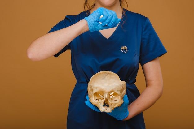 かなり若い医者が人間の頭蓋骨にビタミンカプセルを注ぎます。医者は背景に錠剤を注ぐ。