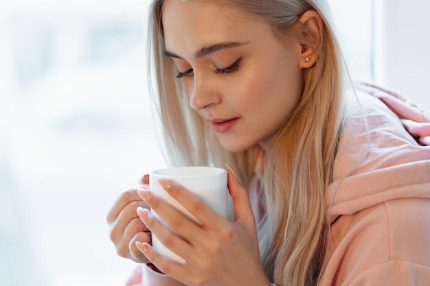 窓際に座ってコーヒーや牛乳を楽しんでいるかわいい少女。カジュアルなピンクの淡いパーカーを着ています。