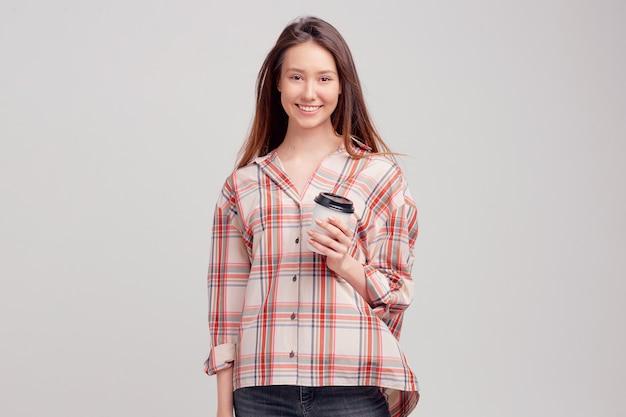 Хорошенькая молодая девушка в повседневной одежде сладко улыбается и держит в одноразовой упаковке стакан кофе.